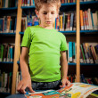 Little boy reading in library — Foto de stock #10376310