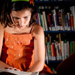 Stock Photo: Young girl reading in library