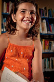 Young girl laughing in a library — Stock Photo