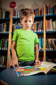 Little boy reading in a library — Stock Photo