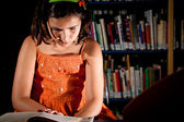 Young girl reading in a library — Stock Photo