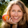 Woman smiling with an apple — Stockfoto