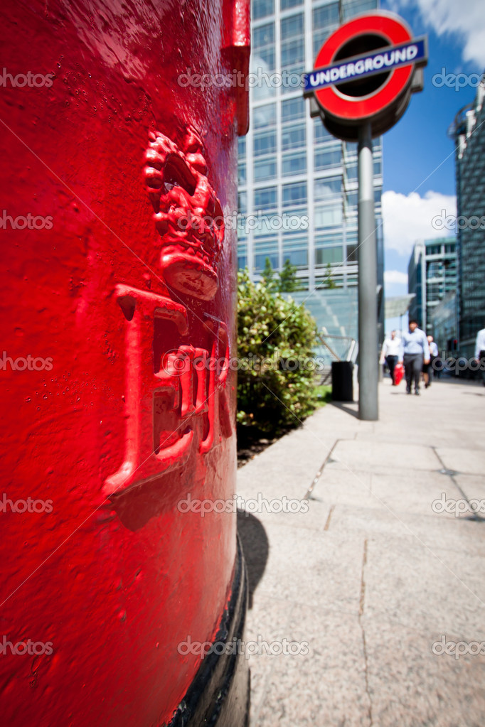 London, 3 June 2011: close-up on a typical red pillar post box in London's financial district of the Docklands. In the background, office workers rushing on and an Underground sign. London's underground railway is the oldest in the world. — Stock Photo #10464460