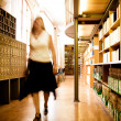 Librarian in a library aisle - Stock Photo