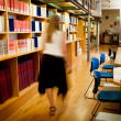 Librarian walking down a library aisle - Stock Photo