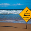 Submerged rocks sign on the beach — Stock Photo