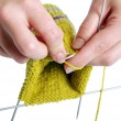 Woman hands knitting a yellow sock on white background — Stock Photo #10264788