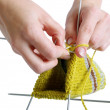 Woman hands knitting a yellow sock on white background — Stock Photo #10264791