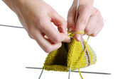 Woman hands knitting a yellow sock on white background — Stockfoto