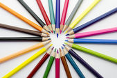 A heart shape made of coloured pencils on white background — Stock Photo
