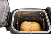 Fresh homemade bread in the electric bread maker on a white back — Stock Photo