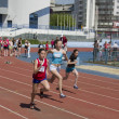 Regional competition in Athletics Champion Juniors of Urals, young women athletes running around the stadium Dynamo. -  