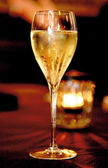 Single bocal of champagne close-up over red background — Stock Photo
