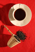 A wicker scoop with herb tea leaves and a cup of tea — Stock Photo