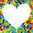 White heart shape with candy background — Stockfoto