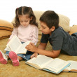 Brother and sister reading books on the floor — Stock Photo