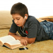 Boy reading and listening music — Stock Photo #10423474