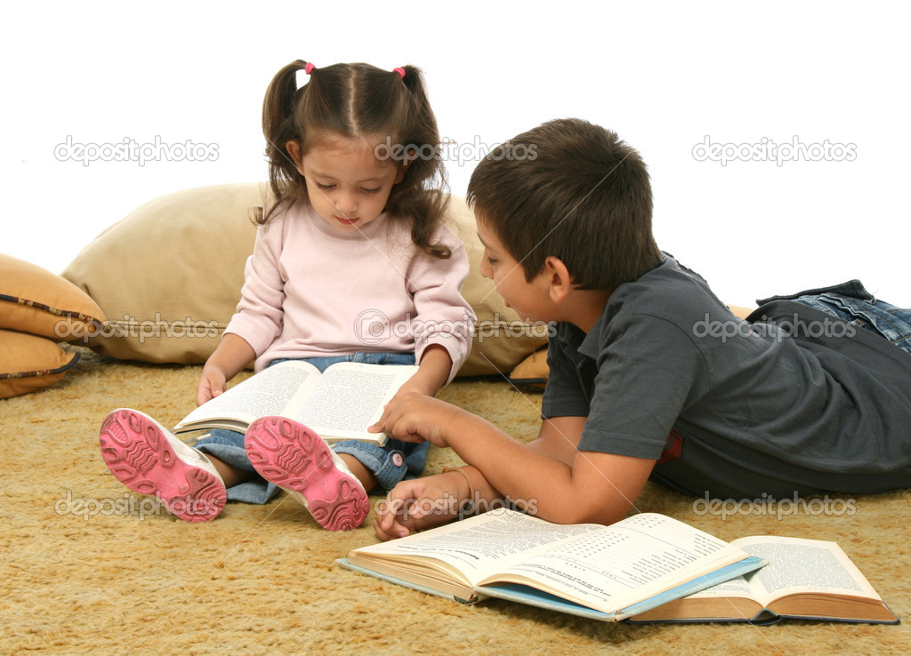 Brother and sister reading books over a carpet. They look interested and concentrated.  Stock Photo #10422483