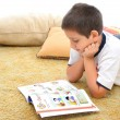 Boy reading a book on the floor — Stock Photo