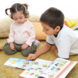 Stock Photo: Brother and sister reading books on the floor