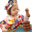 Little girl cooking dressed as a chef — Stock Photo
