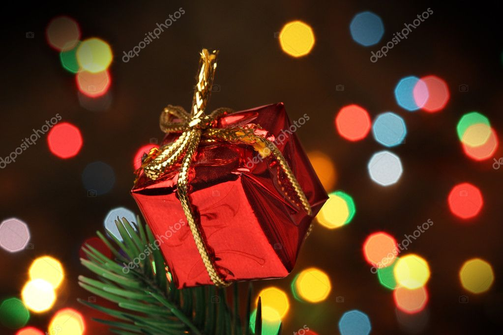 Gift box over a christmas branch tree, lights background — Stock Photo #10499366