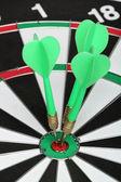 Dartboard bull´s eye. Three darts on center — Foto de Stock