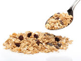 Granola cereals on a spoon over white background — Stock Photo