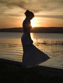 Young, slim lady dances alone at the beach, sunset — Stock Photo