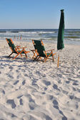 An empty chair and umbrella at the beach — Stock Photo
