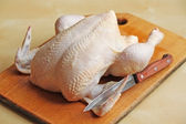 Whole raw chicken on the chopping board with a knife — Stock Photo