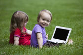 Babies with Notebook sitting on meadow — Stock Photo