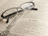 Glasses on the thick old book. — Stock Photo
