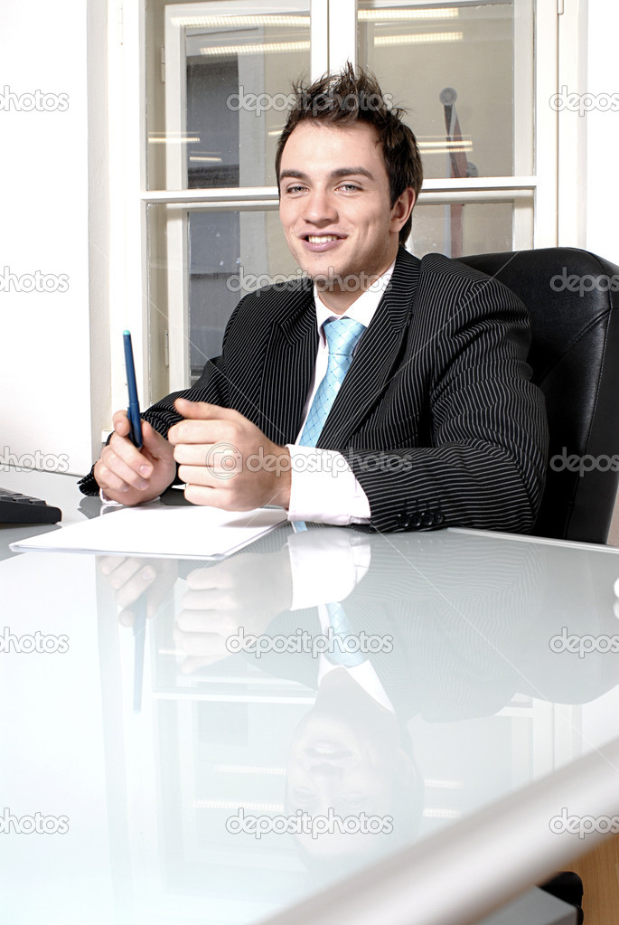 A portrait of a handsome young businessman sitting at the desk in office. — Stock Photo #10329051