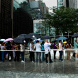 Wait in line under umbrellas — Stock Photo