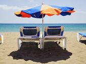 Beach umbrella and deckchairs — Stock Photo