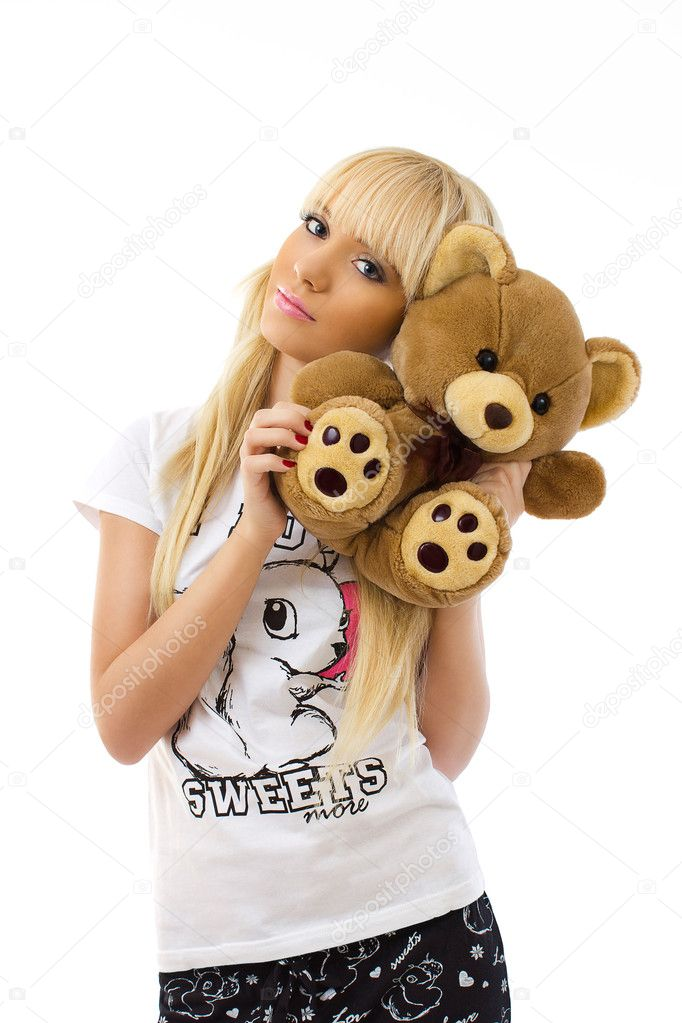 Charming blonde girl wearing pajamas embraces teddy bear on white background  Stock Photo #10343282