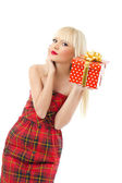 Beautiful young blonde girl holding christmas gift in red dress — Stock Photo