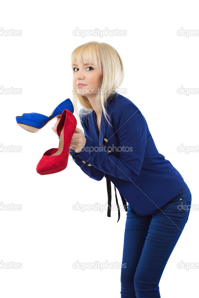 Cute young blonde girl in blue pants and jacket holding shoes smiling isolated on white background — Stock Photo #10357377