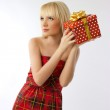 Beautiful blonde girl holding christmas gift in red dress — Stock Photo #10474376