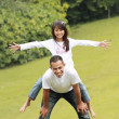 Father giving daughter piggyback ride — Stock Photo