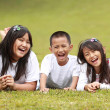 Happy boy and girls lying on a green grass — Stock Photo