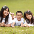 Portrait of happy kids lying on the grass — Stock Photo