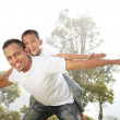 Father giving his son piggyback ride outdoors — Stock Photo #10637879