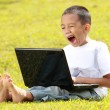 Little boy yawning when playing laptop — Stock Photo #10637891