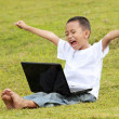 Young little boy celebrating success playing laptop — Stock Photo