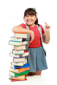 Happy young girl laughing with a pile of books beside her — Stock Photo