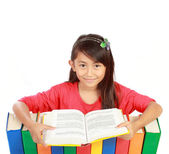 Image of schoolgirl smiling with her books and reading one of th — Stock Photo