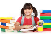 Image of schoolgirl smiling with the heap of books against white — Stock Photo