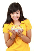Smiling teenage girl holding a bowl of cut fruits — Stock Photo